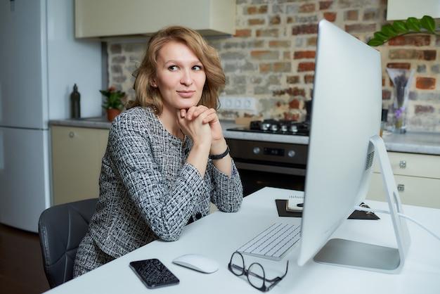 Uma mulher trabalha remotamente em um computador desktop em seu estúdio. uma senhora feliz senta os braços cruzados durante uma videoconferência em casa.