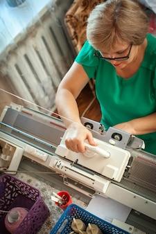 Uma mulher tricota em uma máquina de tricô, trabalhando com as mãos