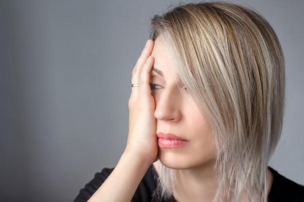 Uma mulher triste com um anel na mão pressiona a mão ao bater