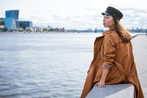 Uma mulher triste e solitária, de aparência europeia, de paletó e boné, senta-se na margem do rio ...