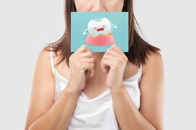 Uma mulher, um papel azul com a imagem dos desenhos animados de dentes de balanço.