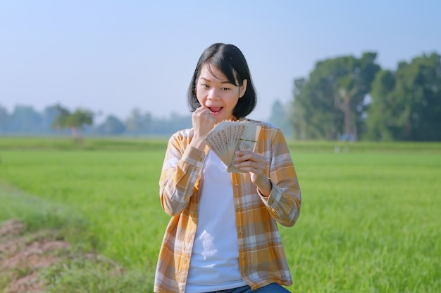 Uma mulher, uma agricultora vestindo uma camisa listrada, está posando de alegria e segurando notas em um campo.