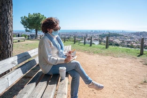 Uma mulher uma máscara cirúrgica, sentada em um banco escrevendo em seu caderno com a cidade
