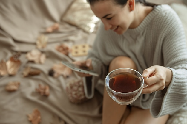Uma mulher usa o telefone e segura uma xícara de chá enquanto está sentada na cama, com um suéter de malha aconchegante, fundo desfocado.