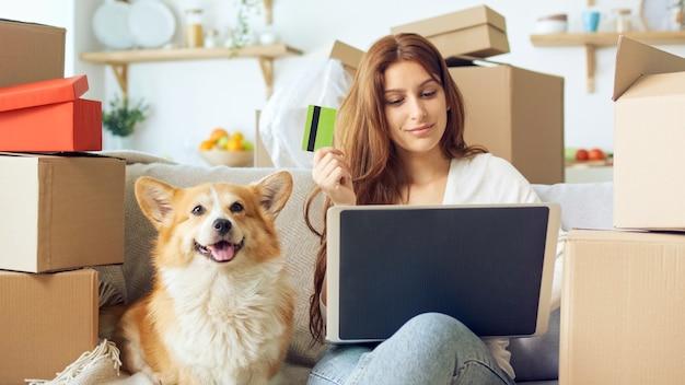 Uma mulher usa um laptop para fazer compras online em casa. confirmação de compra pela internet. vinculando um cartão para compras online. uma mulher sentada no sofá com um cachorro bonito, enquanto fazia compras online.