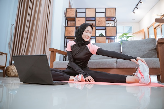 Uma mulher usa uma roupa de ginástica hijab quando está sentada, estende-se com uma perna para o lado e é segurada com uma mão quando está na frente de um laptop em casa