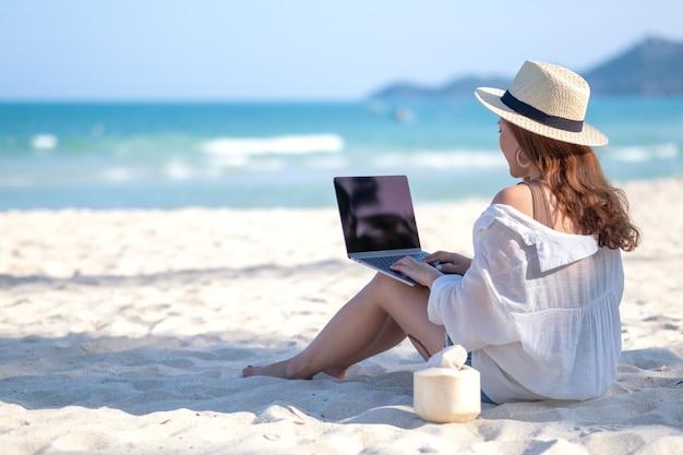 Uma mulher usando e digitando no teclado de um laptop enquanto está sentada em uma bela praia