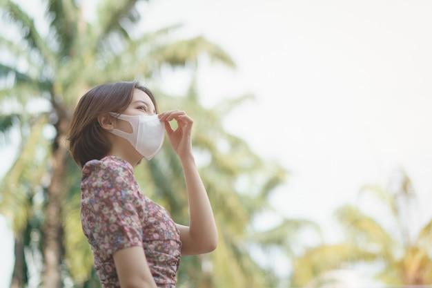 Uma mulher usando máscara facial no parque. vírus corona ou conceito de proteção covid-19.