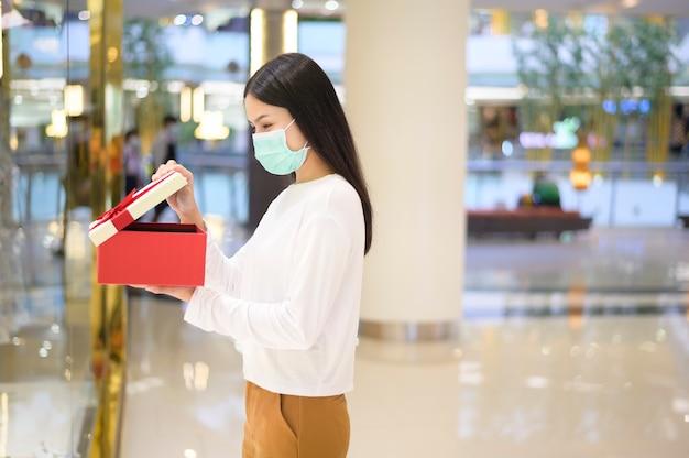 Uma mulher usando máscara protetora segurando uma caixa de presente em um shopping center, sob o conceito de pandemia covid-19, ação de graças e natal.