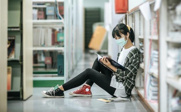 Uma mulher usando máscaras está sentada lendo um livro na biblioteca.