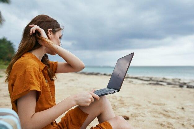 Uma mulher usando o laptop na praia tropical com palmeiras