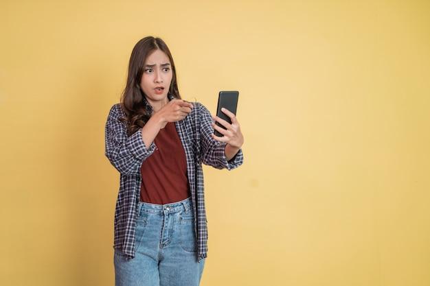 Uma mulher usando um celular com um gesto de surpresa e apontando o dedo enquanto olha para um celular ...