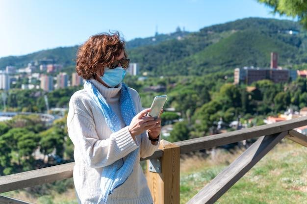 Uma mulher usando uma máscara cirúrgica, tirando fotos com seu smartphone em um mirante de montanha com vista para a cidade