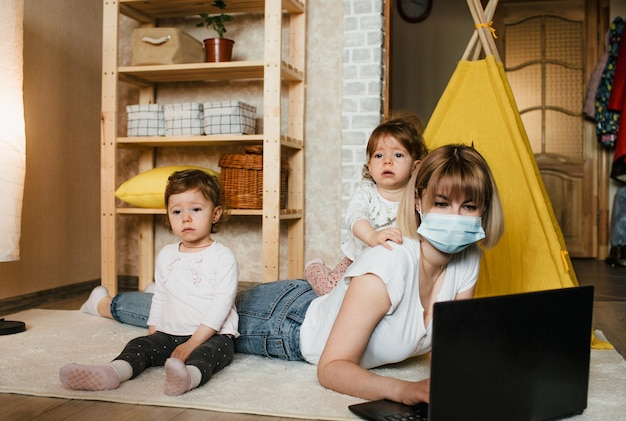 Uma mulher usando uma máscara médica trabalha em um computador em casa com dois filhos pequenos