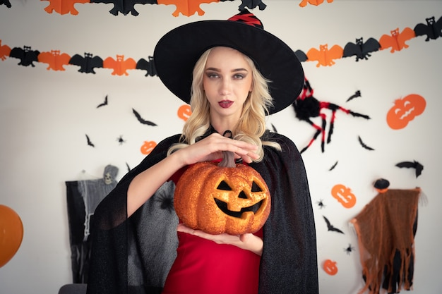 Uma mulher vestida de bruxa segurando uma festa de abóbora