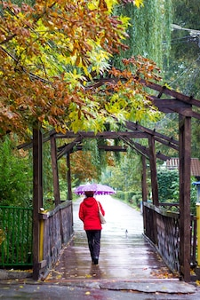 Uma mulher vestindo roupas vermelhas com um guarda-chuva durante a chuva dá um passeio no parque da cidade