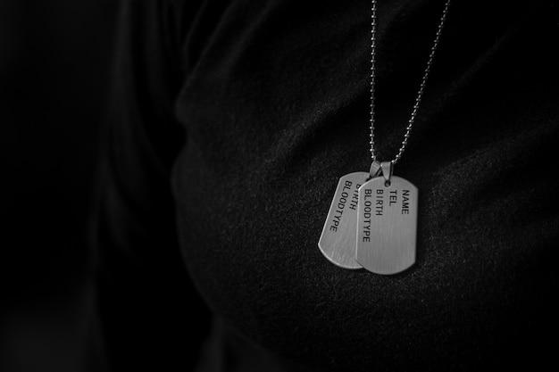 Uma mulher vestindo um tag de cão militar em branco. - conceito de memórias e sacrifícios.