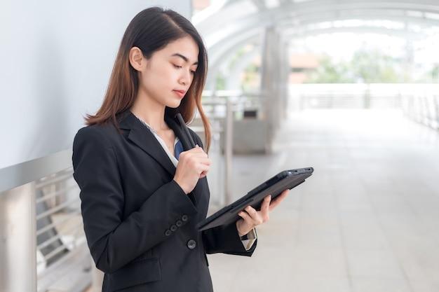 Uma mulher vestindo um terno preto está olhando pensativamente para o tablet.