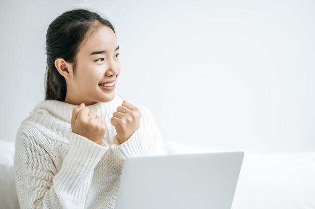 Uma mulher vestindo uma camisa branca em cima da cama e jogando laptop alegremente.