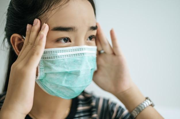 Uma mulher vestindo uma camisa listrada, vestindo uma máscara.