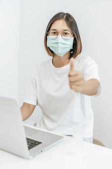 Uma mulher vestindo uma máscara jogando um laptop e polegares para cima.