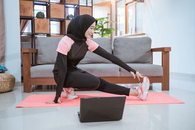 Uma mulher vestindo uma roupa de ginástica hijab ao se agachar se alonga com uma perna puxada para o lado e segurada com uma mão quando na frente de um laptop em casa
