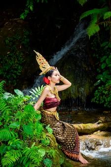Uma mulher vestiu-se com um vestido tailandês antigo na cachoeira.
