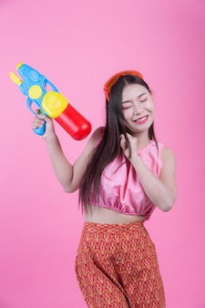Uma mulher vestiu-se em uma roupa popular tailandesa tradicional que guardara uma arma de água em um fundo cor-de-rosa.
