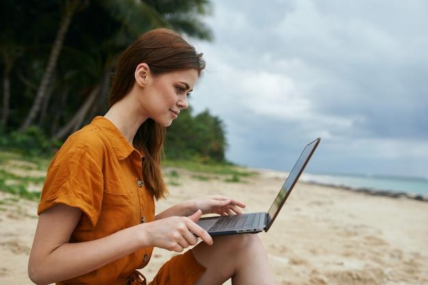 Uma mulher viaja com um laptop ao longo do oceano ao longo da areia com palmeiras