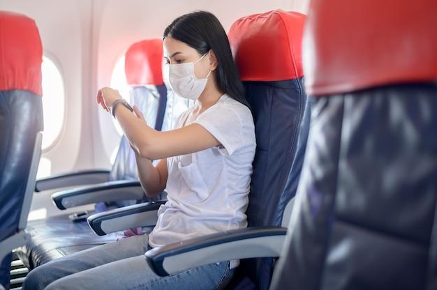 Uma mulher viajando usando máscara protetora a bordo da aeronave usando relógio inteligente, viagem sob a pandemia covid-19, viagens de segurança, protocolo de distanciamento social, novo conceito de viagem normal