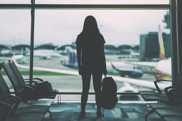 Uma mulher viajante com mochila no aeroporto