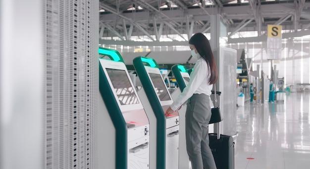 Uma mulher viajante está usando máscara protetora no aeroporto internacional, viaja sob a pandemia de covid-19.