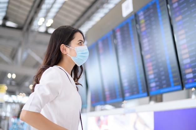Uma mulher viajante está usando máscara protetora no aeroporto internacional, viajando sob a pandemia de covid-19,