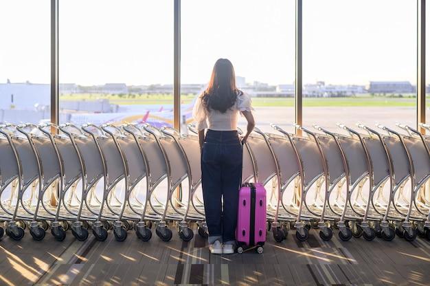 Uma mulher viajante está usando máscara protetora no aeroporto internacional, viajando sob a pandemia de covid-19