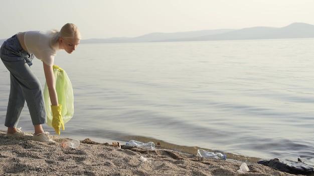 Uma mulher voluntária com luvas de borracha e um saco plástico nas mãos coleta lixo na margem do lago. purificação de reservatórios e do meio ambiente. 4k uhd
