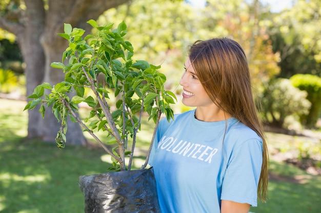 Uma mulher voluntária segurando uma planta