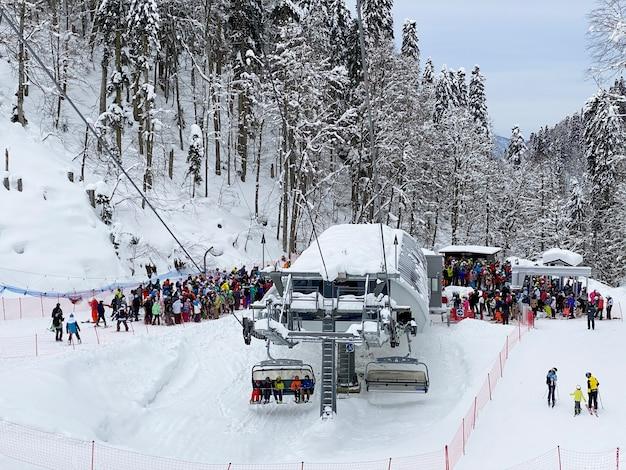 Uma multidão de esquiadores e praticantes de snowboard em uma longa multidão para o teleférico