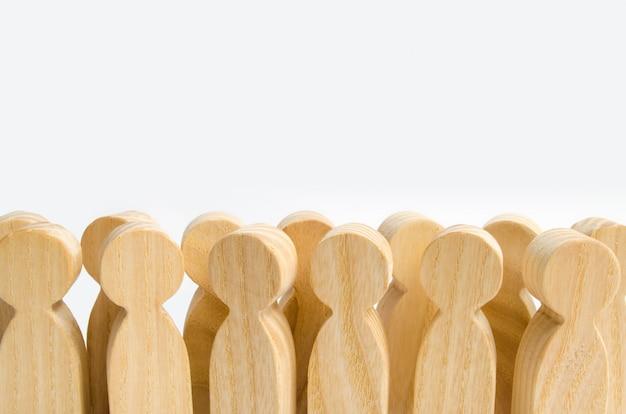 Uma multidão de figuras de madeira dos povos que estão em um fundo branco.