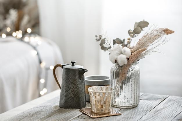 Uma natureza morta aconchegante com detalhes decorativos e um buquê de flores secas no interior de um quarto em estilo escandinavo.