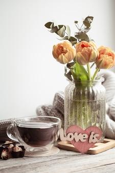 Uma natureza morta festiva com a inscrição love it, flores em um vaso e uma xícara de chá e detalhes de decoração.