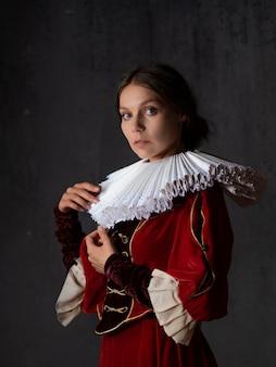 Uma nobre senhora com um luxuoso vestido vermelho, estilo medieval, uma jovem com uma gola redonda espanhola, um retrato no estilo das pinturas renascentistas