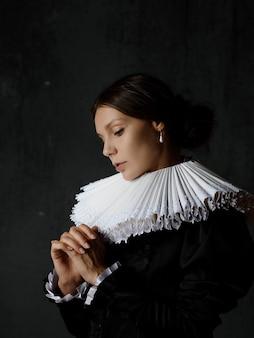 Uma nobre senhora com um traje medieval, uma jovem com um colarinho espanhol redondo, um retrato no estilo das pinturas renascentistas