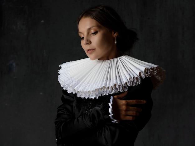 Uma nobre senhora com um traje medieval, uma jovem com um colarinho espanhol redondo