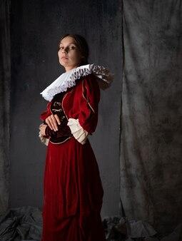 Uma nobre senhora em um luxuoso vestido vermelho estilo medieval uma jovem mulher