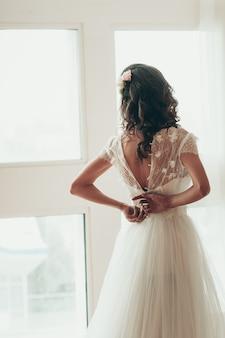 Uma noiva abotoando o vestido ao lado de uma janela, vista das costas