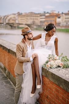 Uma noiva afro-americana se senta em uma parede de tijolos e um noivo caucasiano a abraça. a barragem do rio arno, com vista para a cidade e pontes. casal de noivos inter-raciais