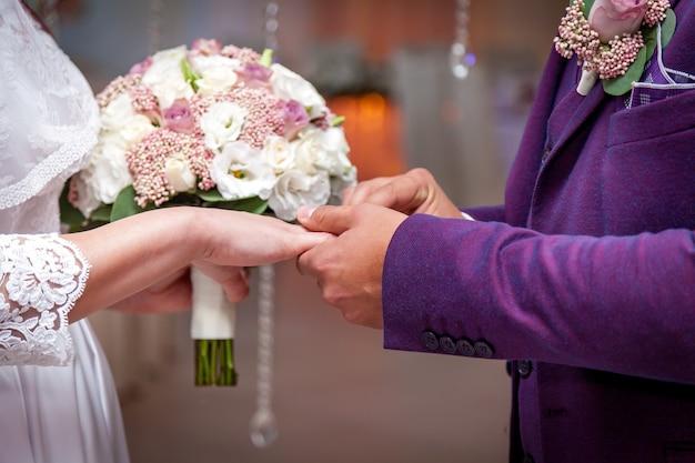 Uma noiva colocando um anel no dedo do noivo durante a cerimônia de casamento.