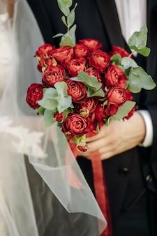 Uma noiva com um lindo vestido segurando um buquê de flores