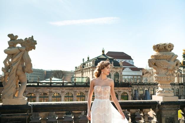 Uma noiva com um vestido branco em uma caminhada de casamento no famoso palácio barroco zwinger em dresden, saxônia, alemanha