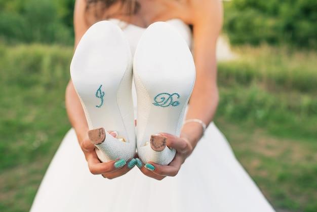 Uma noiva com um vestido branco segura os sapatos na frente dela de perto